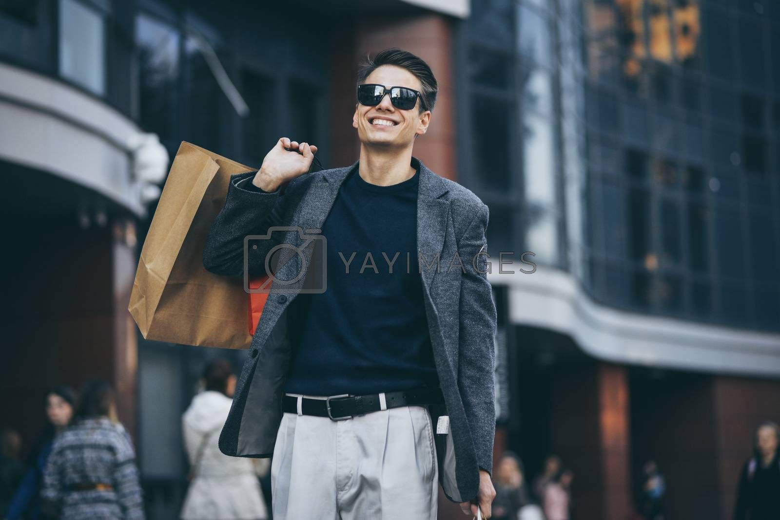 Serious cool guy with sunglasses and paper bags walking at street.