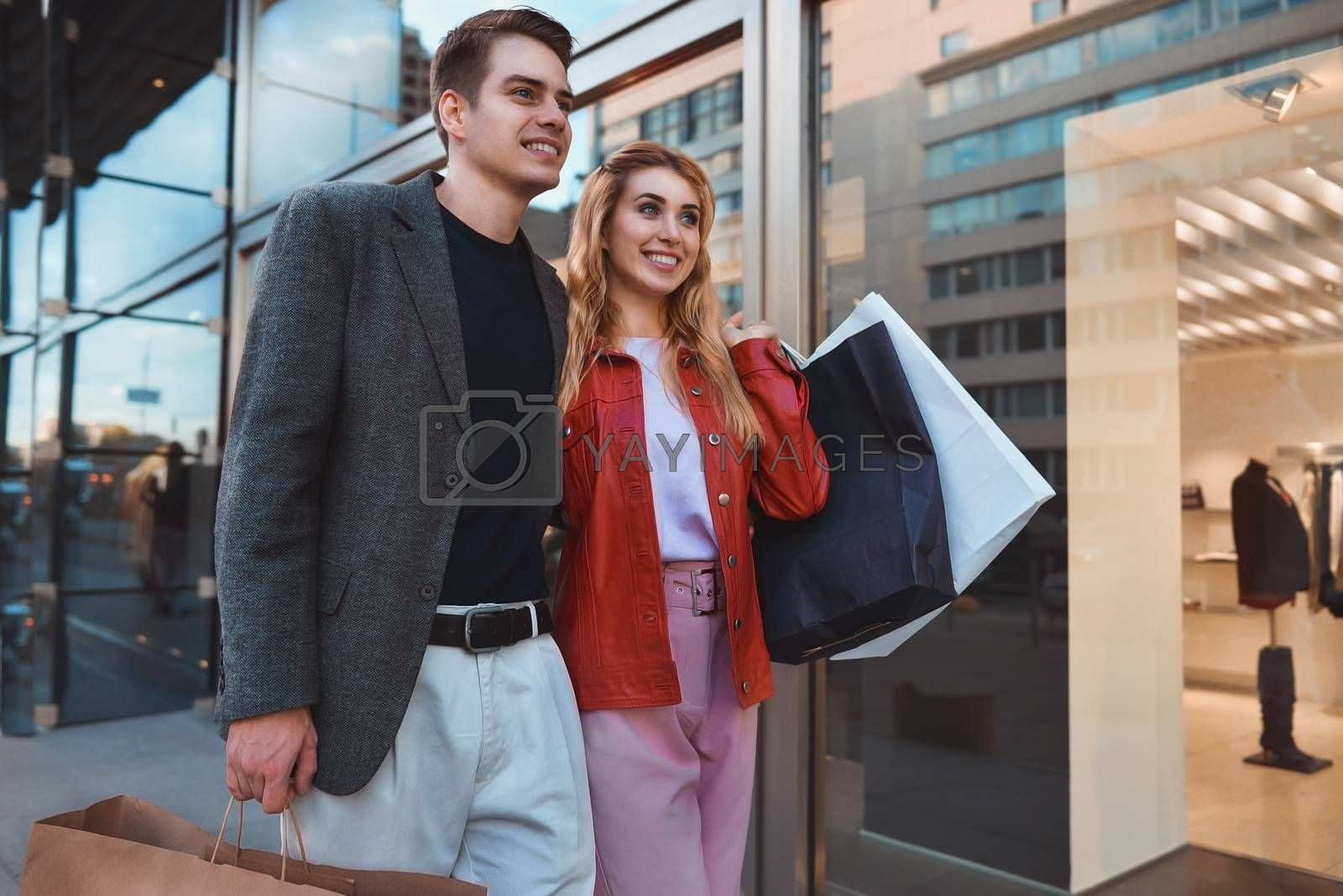 Beautiful couple with shopping bags is talking and smiling while doing shopping in the mall focus on the woman