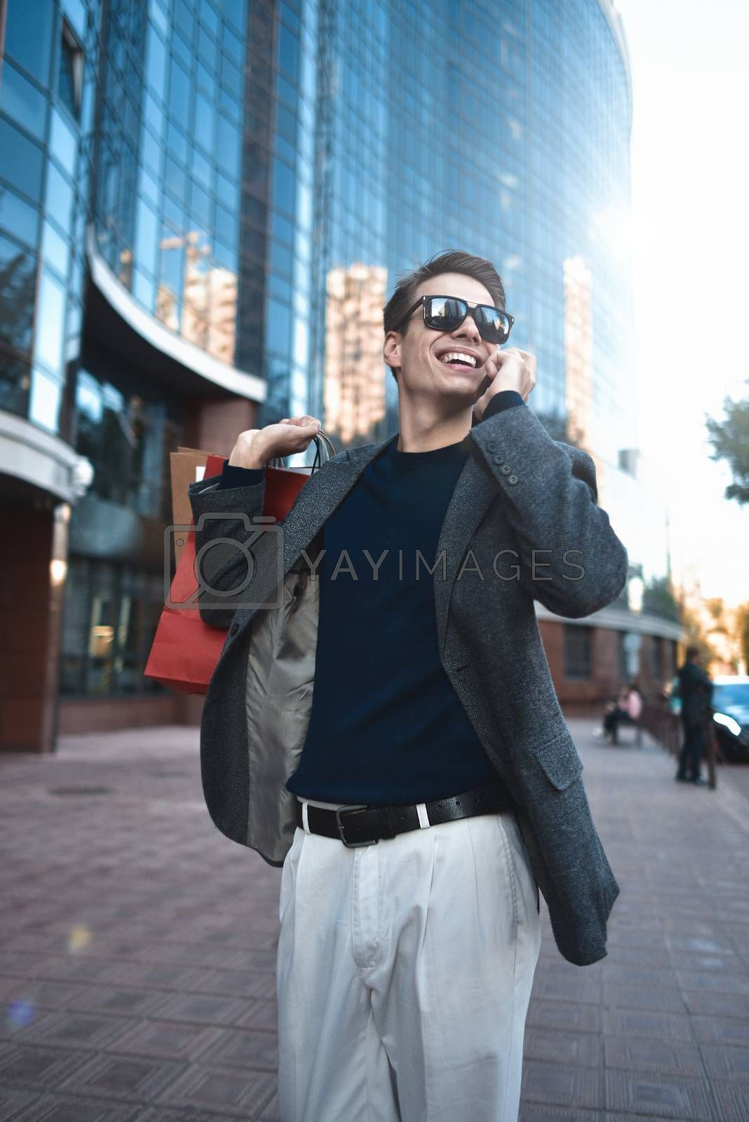 Positive cool guy with sunglasses and paper bags walking near showcase with reflection.