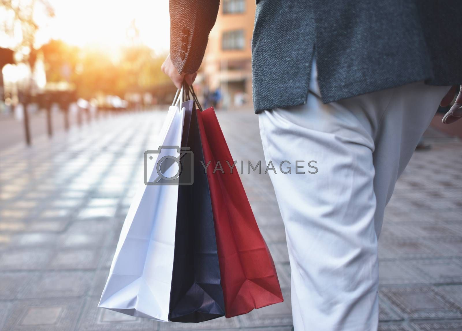 Close up of a young caucasian man holding some different paper shopping bags in the street.