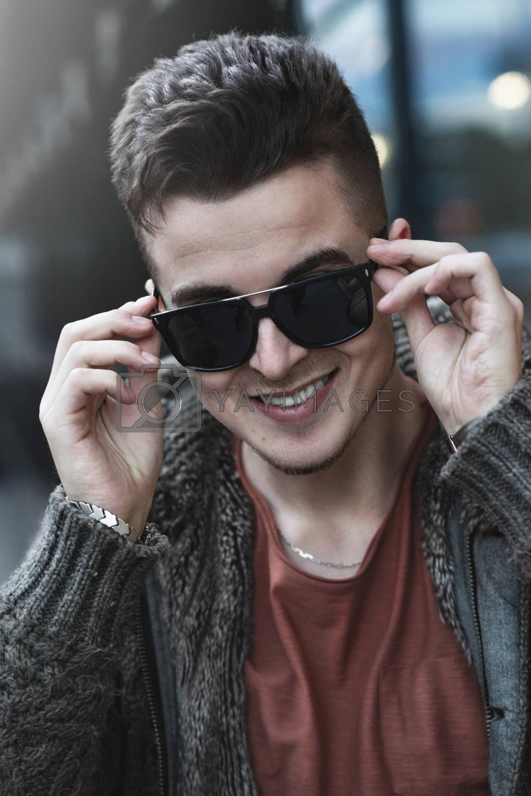 Closeup of cheerful young caucasian man in sunglasses standing and smiling over street background