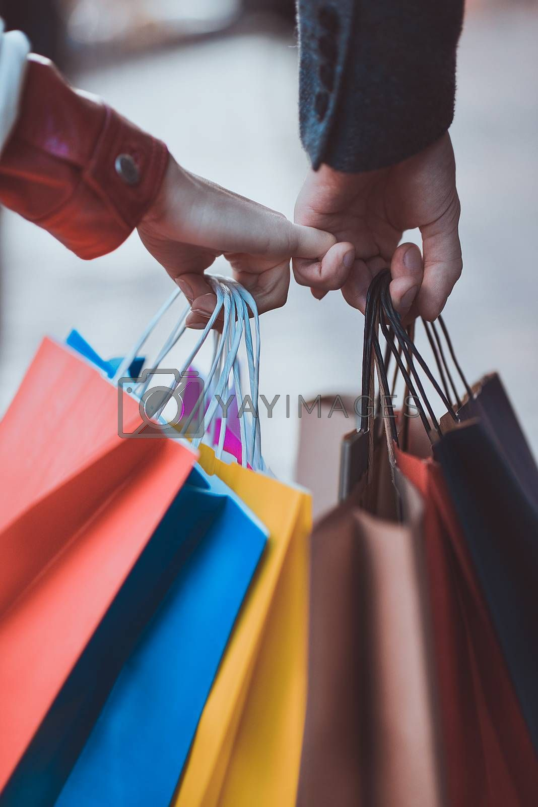 Colorful paper bags in hands of couple. Shopping and sales concept.