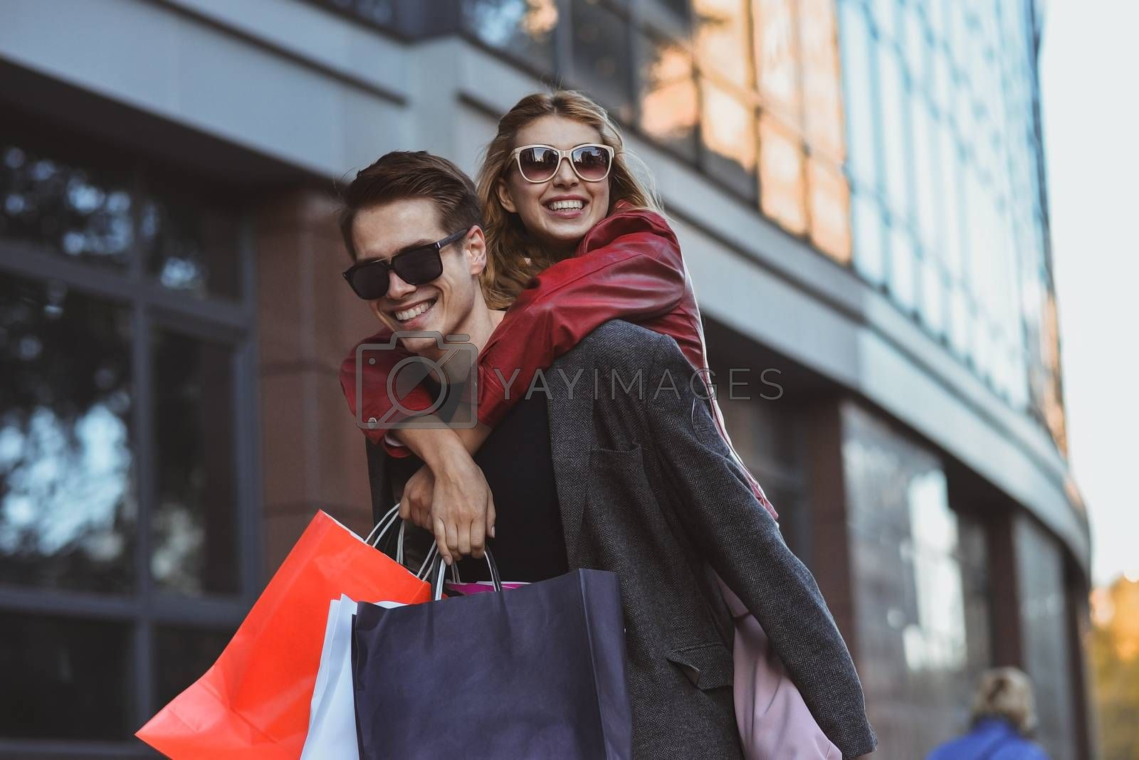 Happy couple shopping together and having fun. Boyfriend carrying his girlfriend on the piggyback.