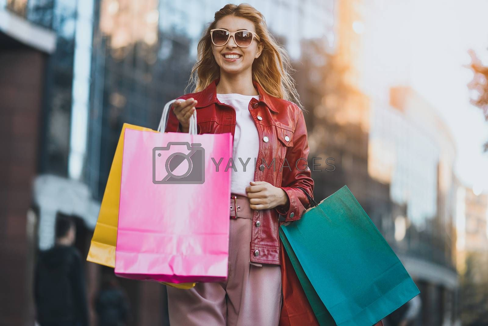 Shopping woman walking outside at street holding shopping bags. Shopper smiling happy walking the street after shopping