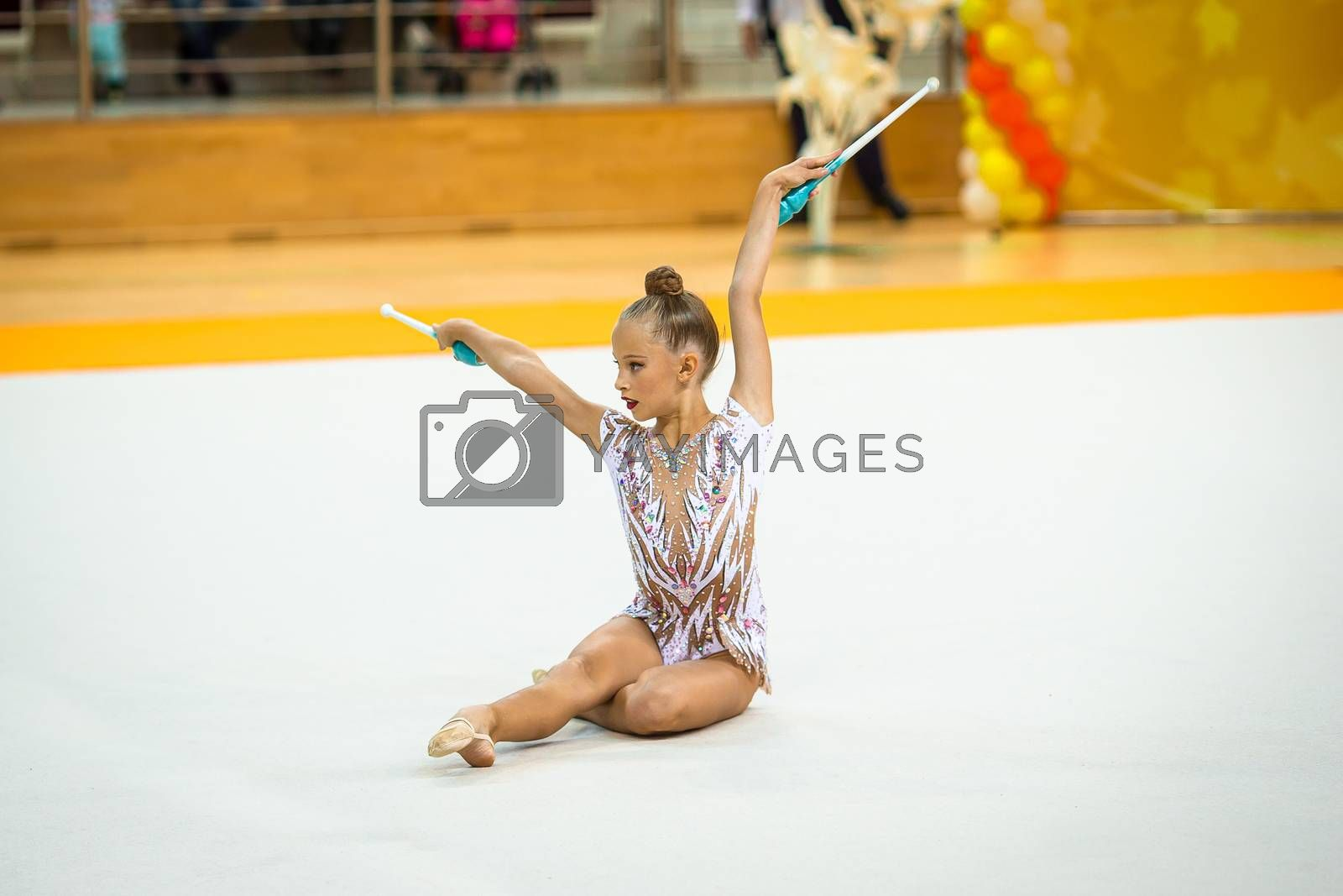 Beautiful little gymnast girl with her performance on the carpet