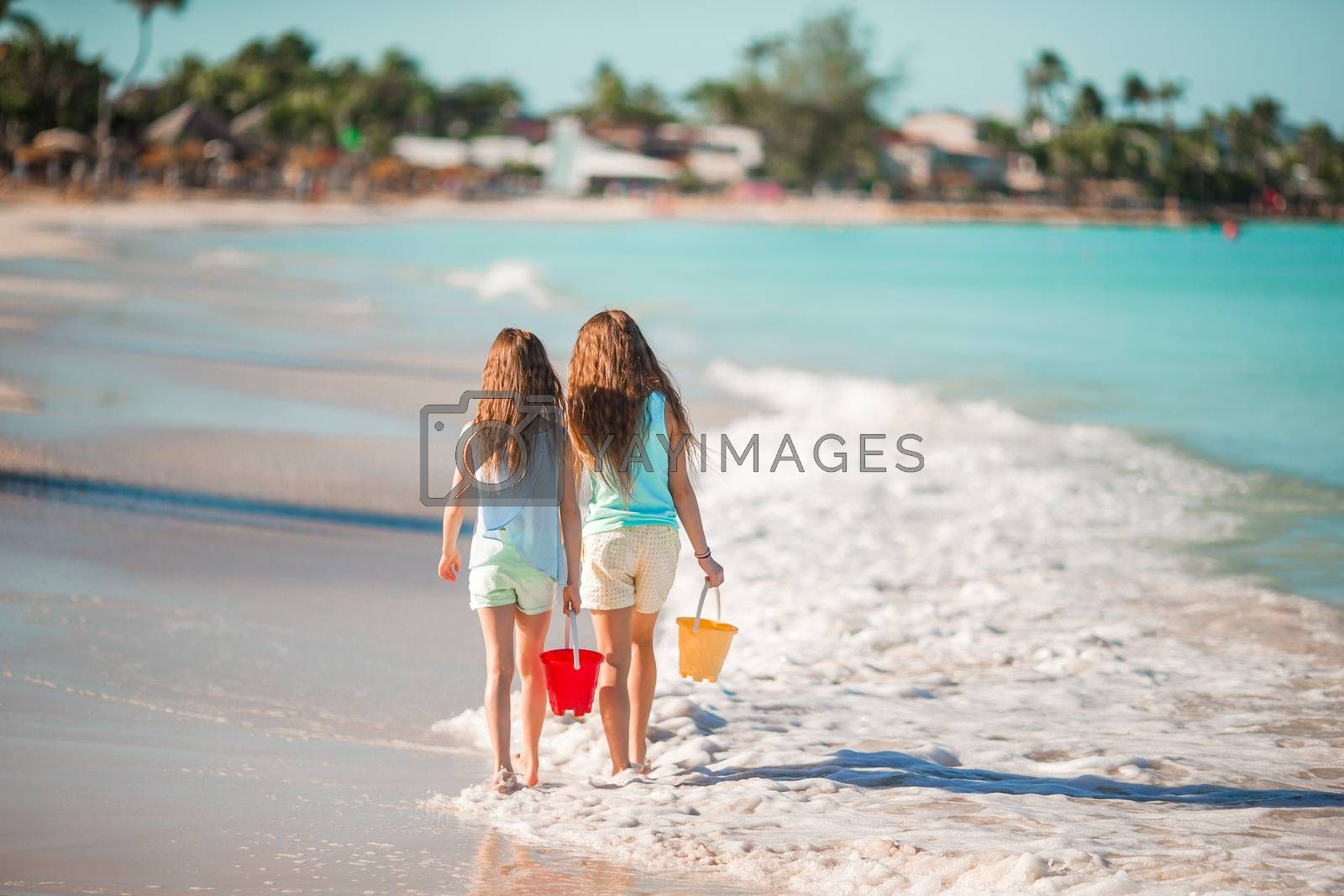 Adorable little girls playing with sand on the beach. Back view of kids walking along the beach