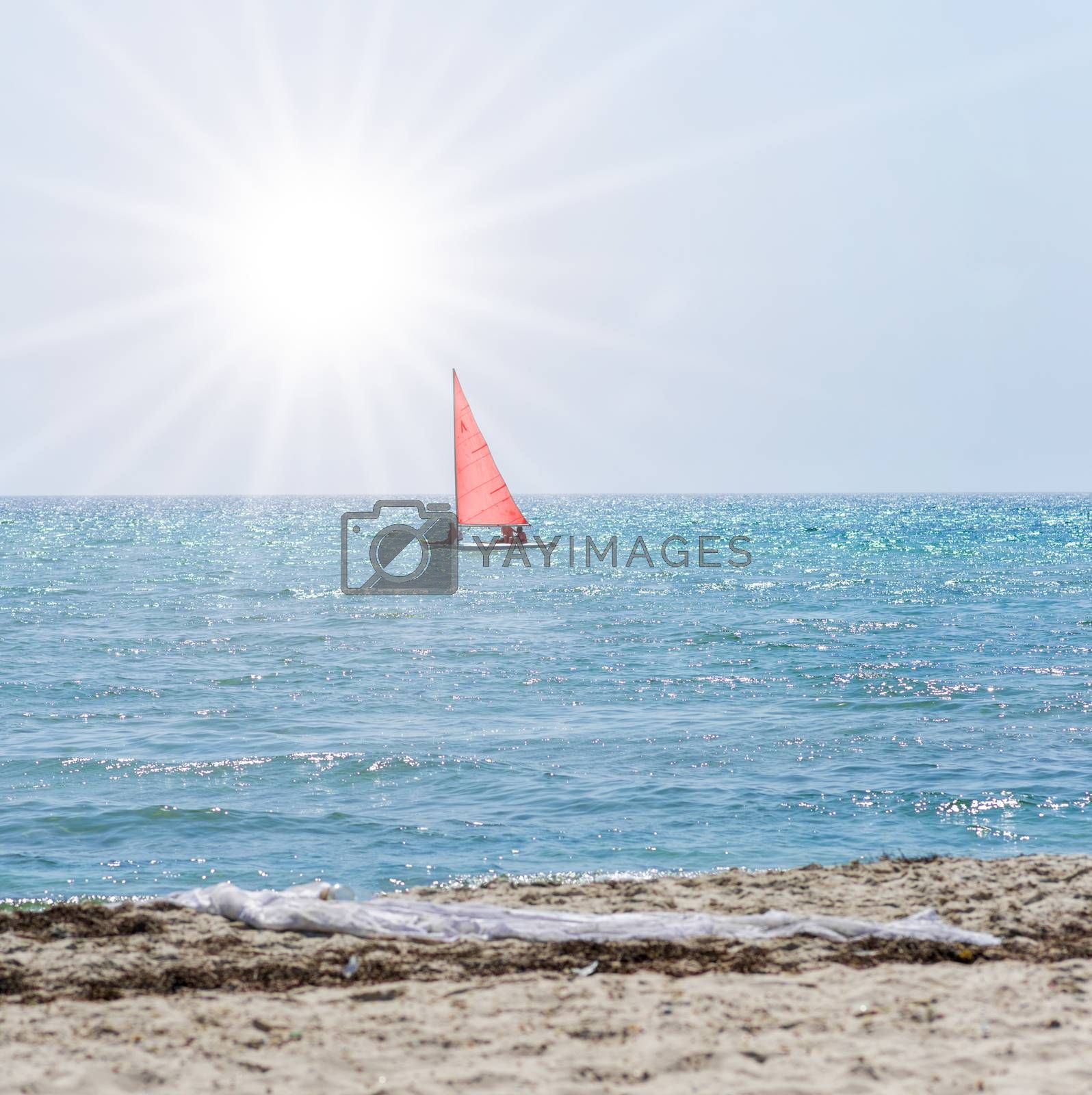 boat with red sails swims away by the sea  by ndanko