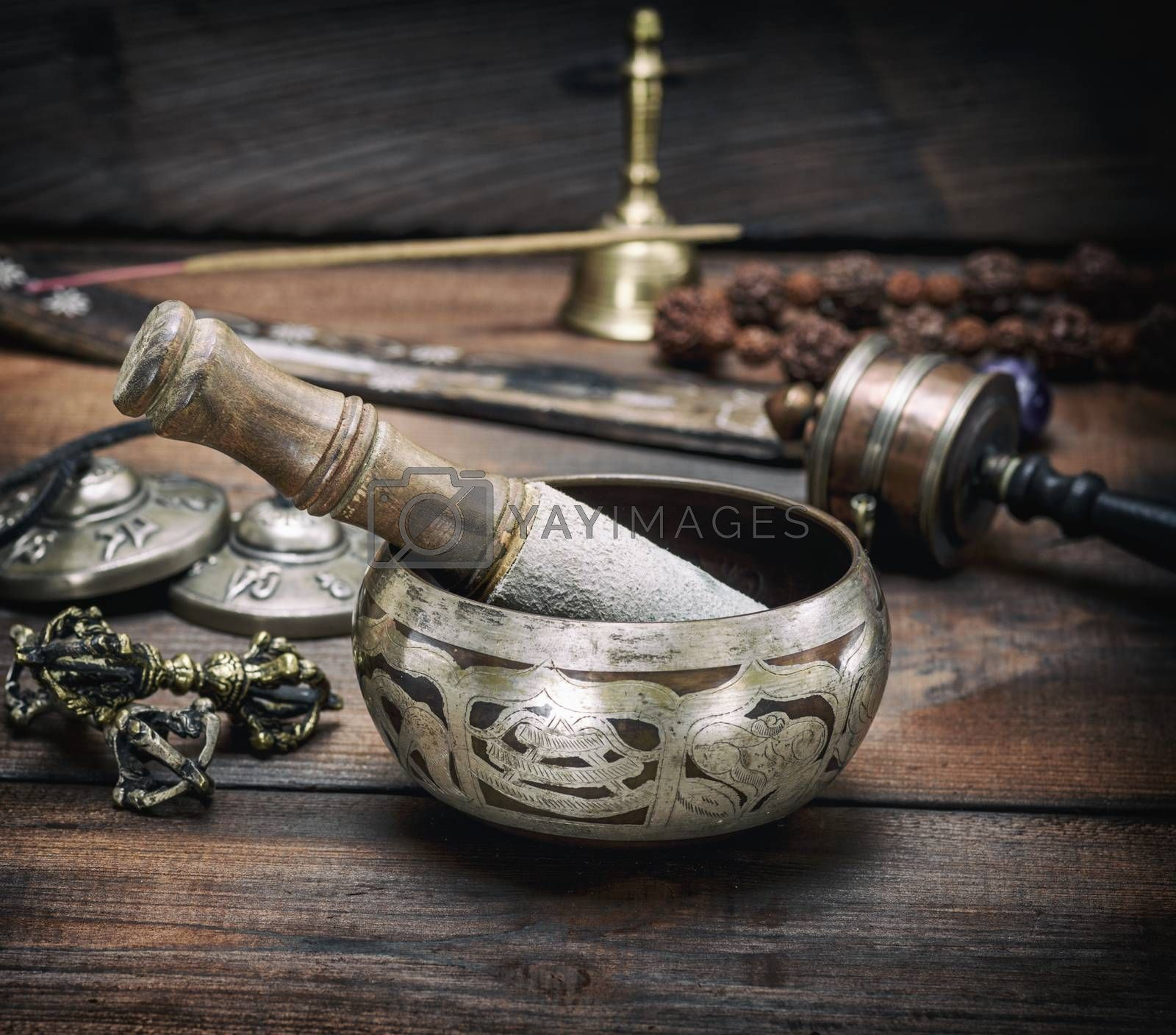 copper singing bowl and a wooden stick on a brown table by ndanko