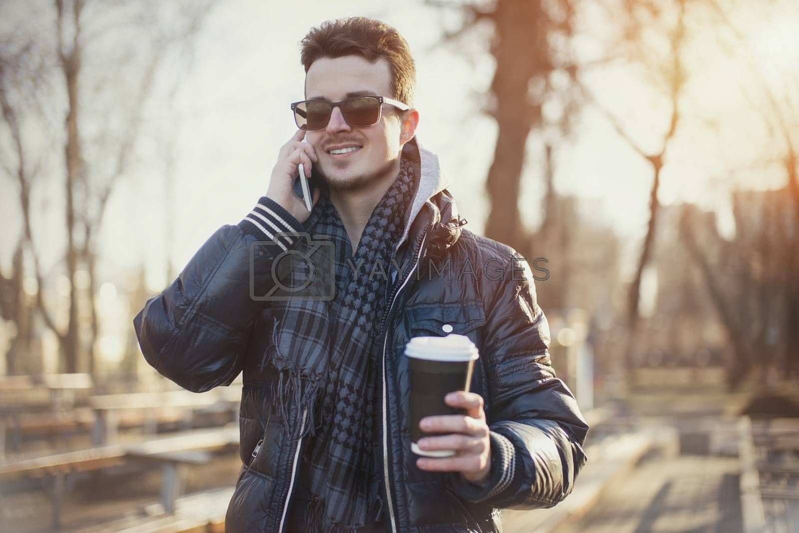 Portrait of attractive man in wearing jacket using mobile phone and holding takeaway coffee while walking through city street.
