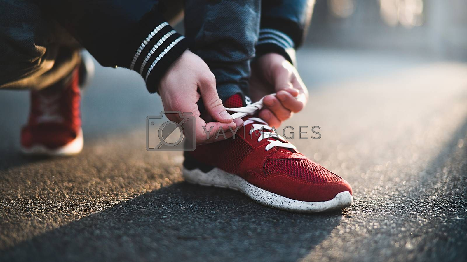 Unrecognizable man stopping lacing shoe outdoors. Athletic shoes concept. Jogging in the park