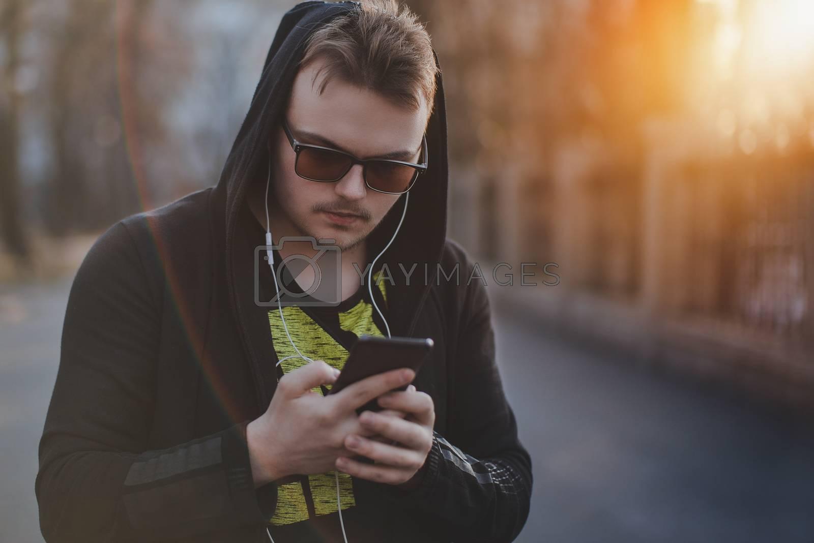 Man in Hood with headphones looking at smartphone.