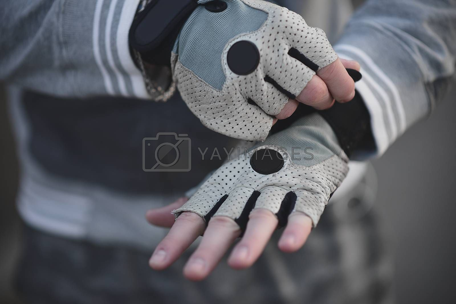 A Man on the street puts on his hands sports gloves and prepares for coaching.