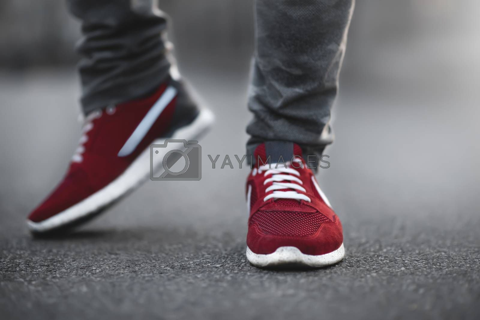 Sports red sneakers close-up on asphalt. Legs and shoes from the lower angle
