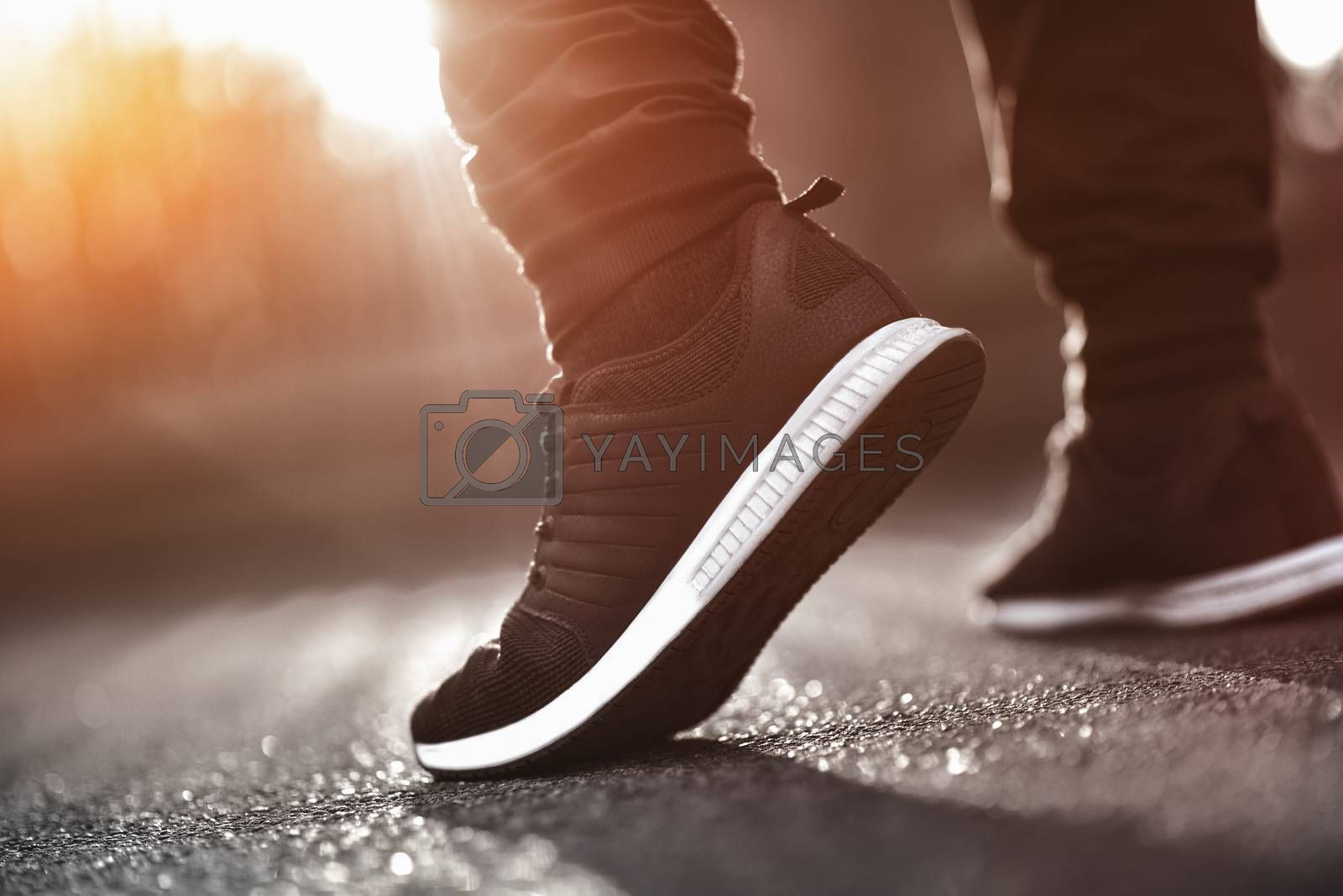 Man in sneakers walks down the street on a sunny day
