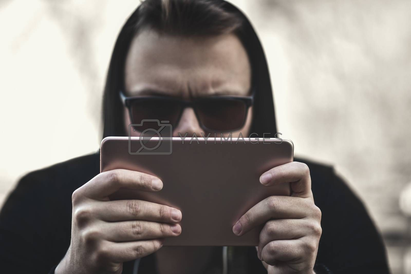 Closeup of a guy in a black hood and a tablet in his hands running on a tablet.