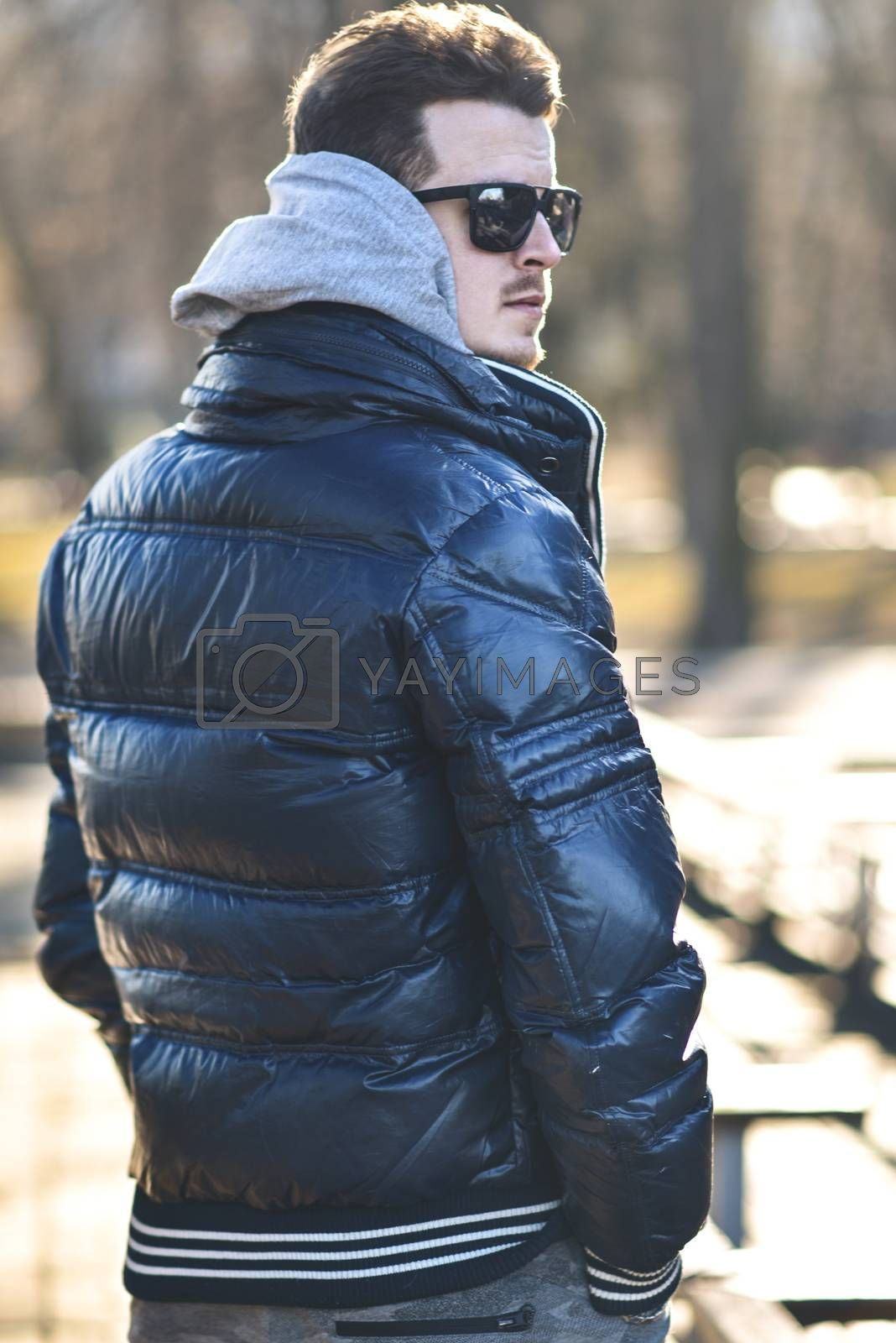 Portrait of attractive man in sunglasses with casual clothes walk in park