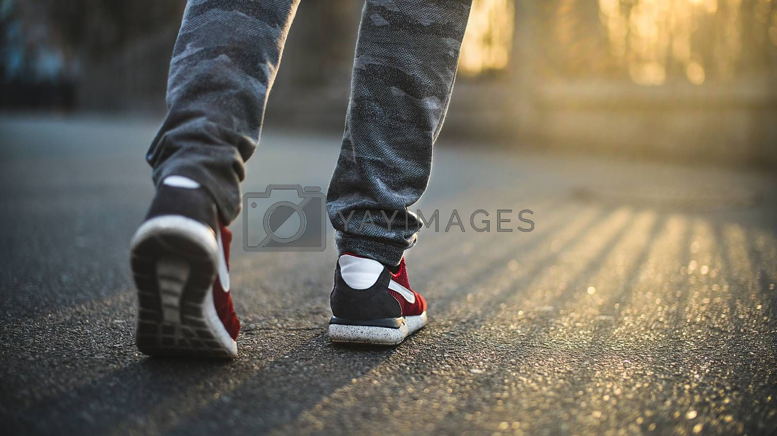 Man in red sport sneakers walks down the street on a sunny day