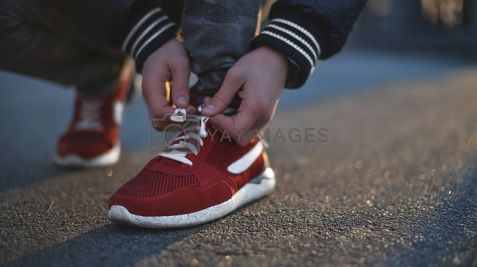Hands of sportsman with pedometer tying shoelaces on sporty sneaker. Running equipment concept. Shoelaces tying by male hands.