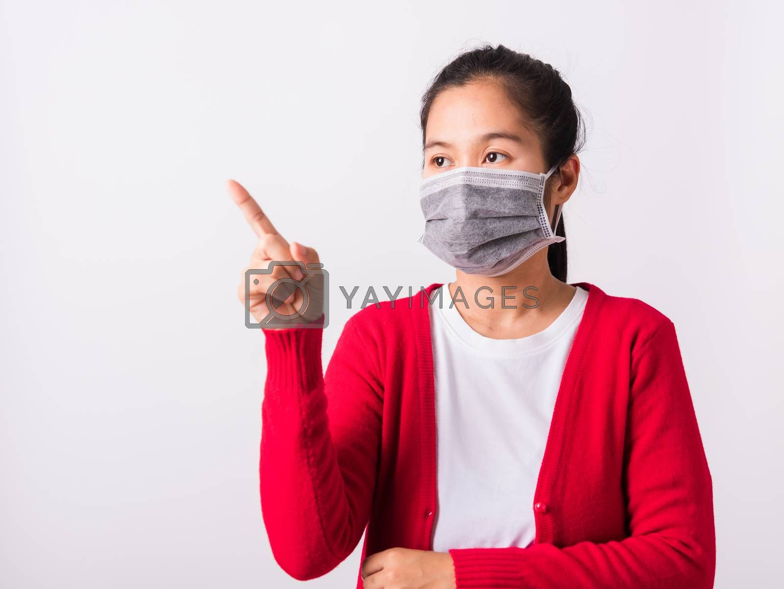 Asian adult woman wearing red shirt and face mask protective against coronavirus or COVID-19 virus or filter dust, air pollution her point finger to side space, studio shot isolated white background