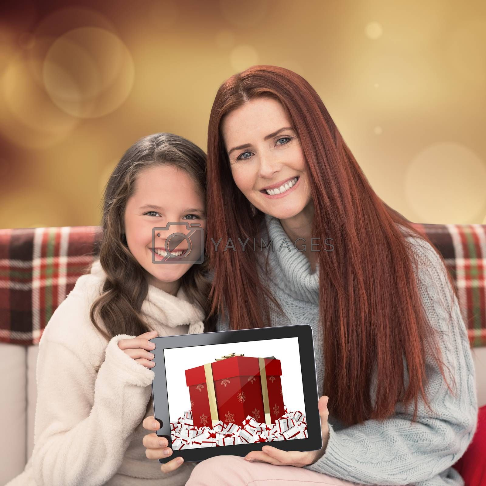 Mother and daughter showing tablet against orange abstract light spot design