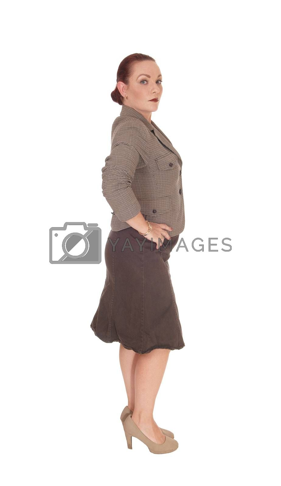 A pretty business woman standing full length in the studio and looking into the camera, isolated for white background