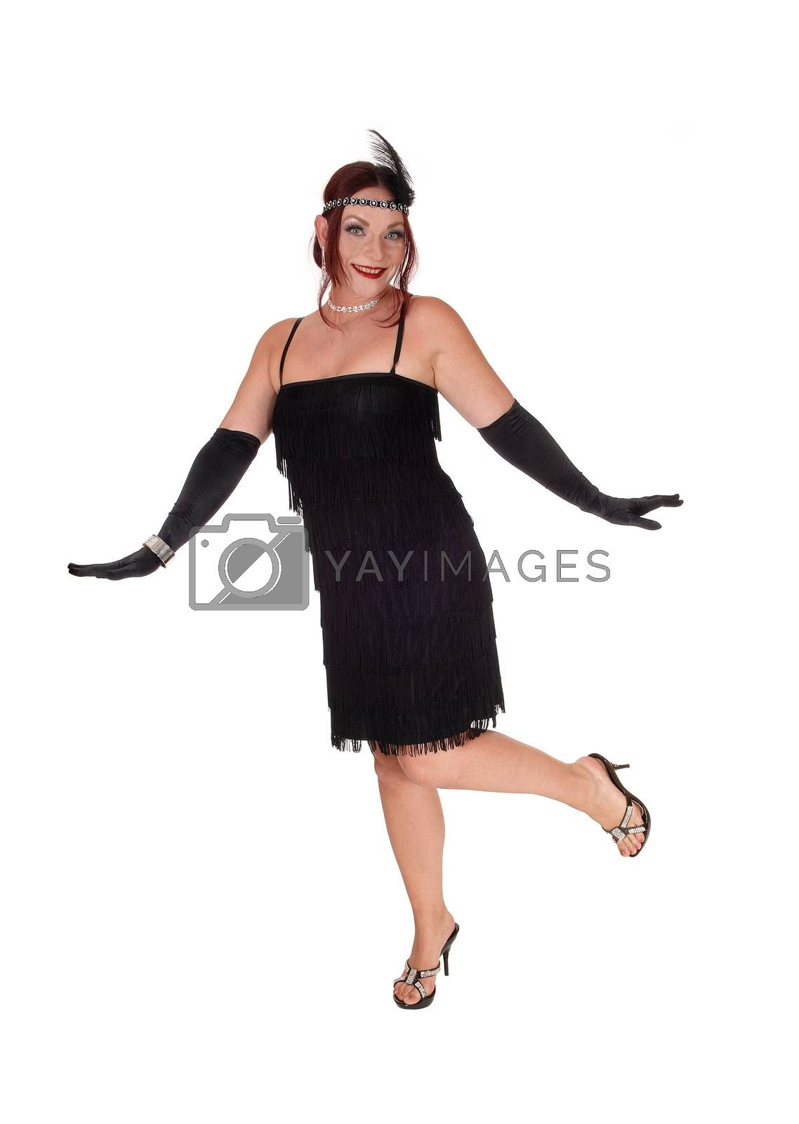A gorgeous woman in a black dress of the 20 century and long cloves dancing in the studio, isolated for white background