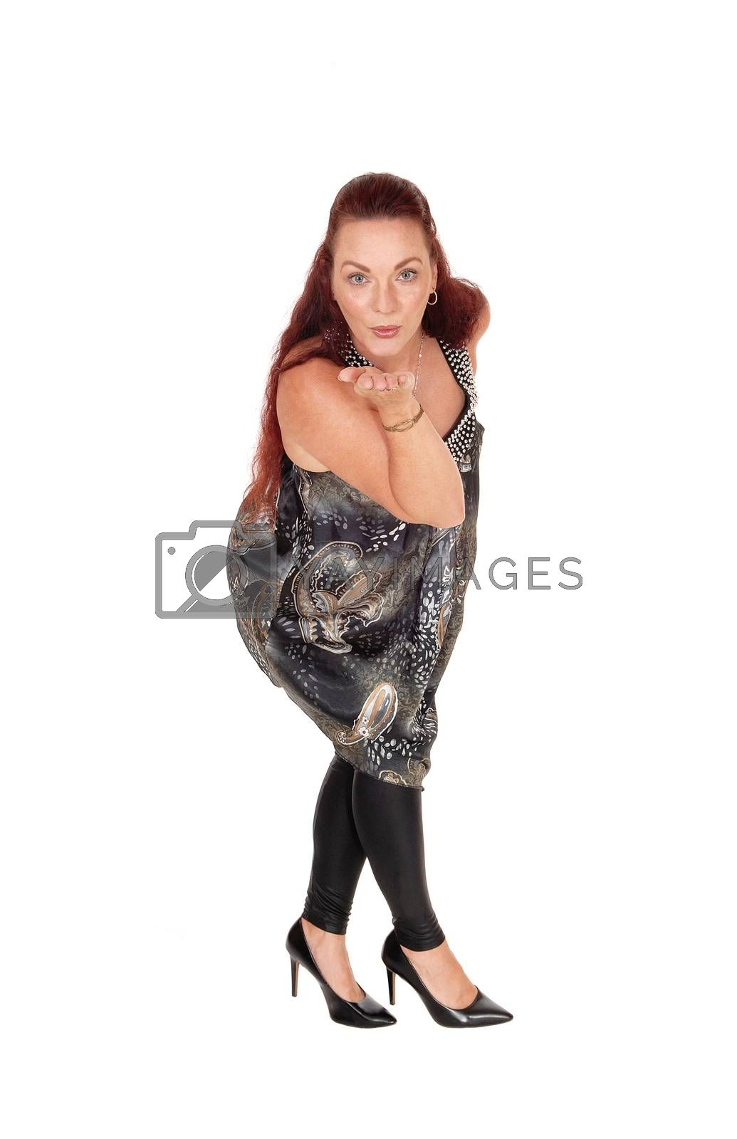 A beautiful middle age woman standing in a gray dress  blowing a kiss, with her red hair, isolated for white background