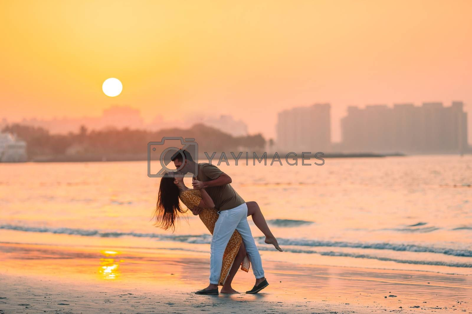 Family vacation. Young couple enjoy beach at sunset kissing
