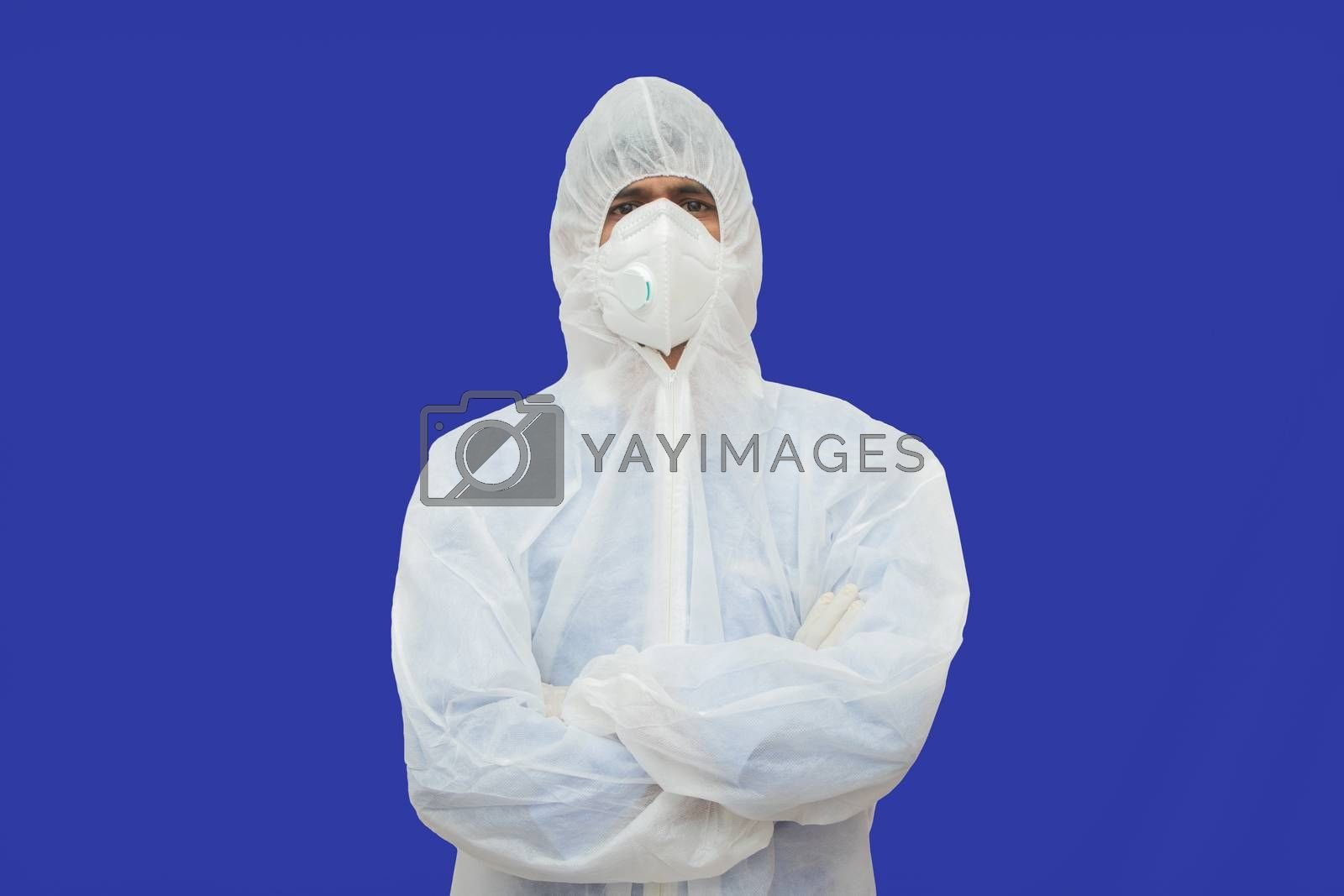 Confident epidemiologist in hazmat suit with medical face mask - Concept to fight covid-19 or coronavirus outbreak by controlling virus spread. by lakshmiprasad