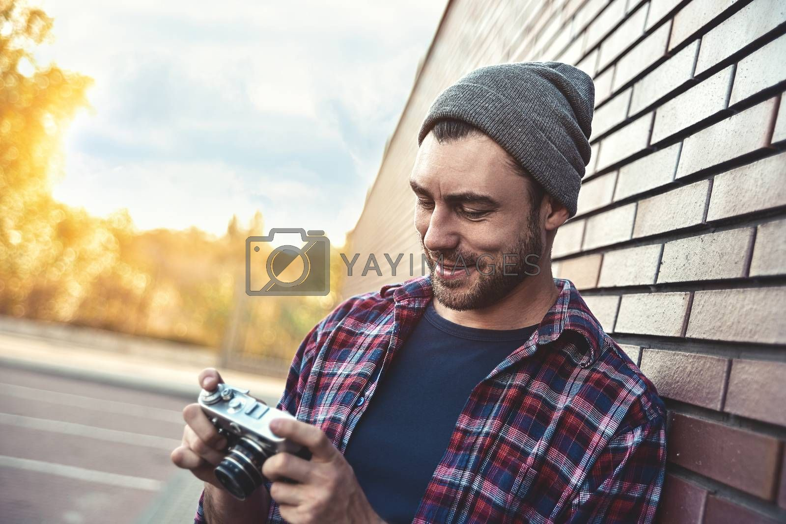 Smiling man with retro photo camera Fashion Travel Lifestyle outdoor while standing against brick wall background