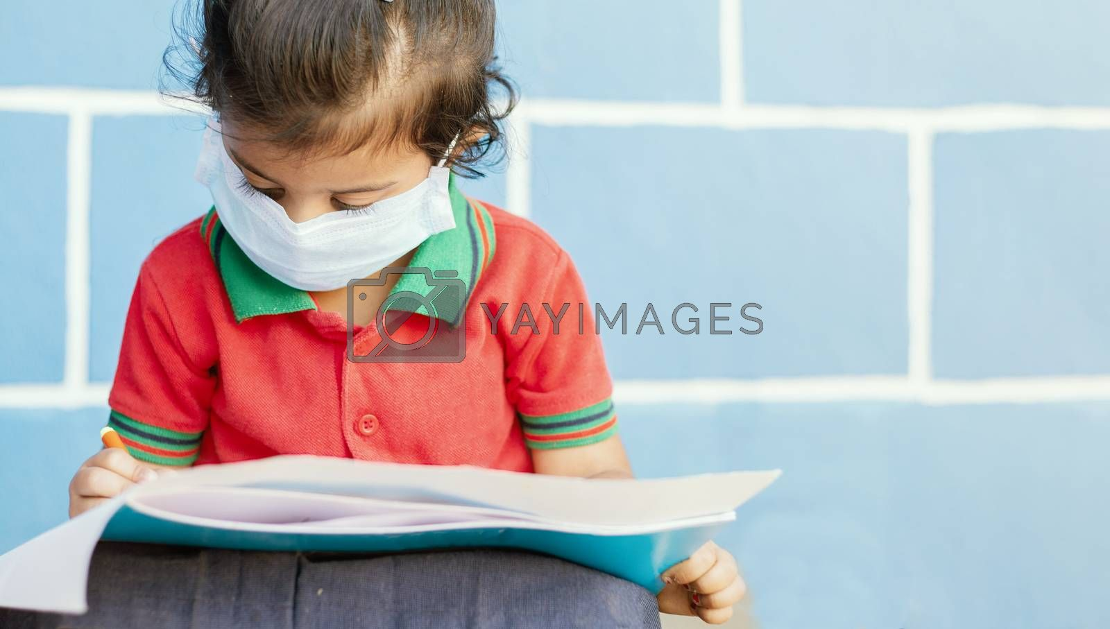 Covid 19 or Coronavirus and Air pollution pm2.5 concept - Little girl wearing medical mask and busy in writing at school - showing Wuhan covid-19 or sars cov 19 outbreak or epidemic of virus. by lakshmiprasad