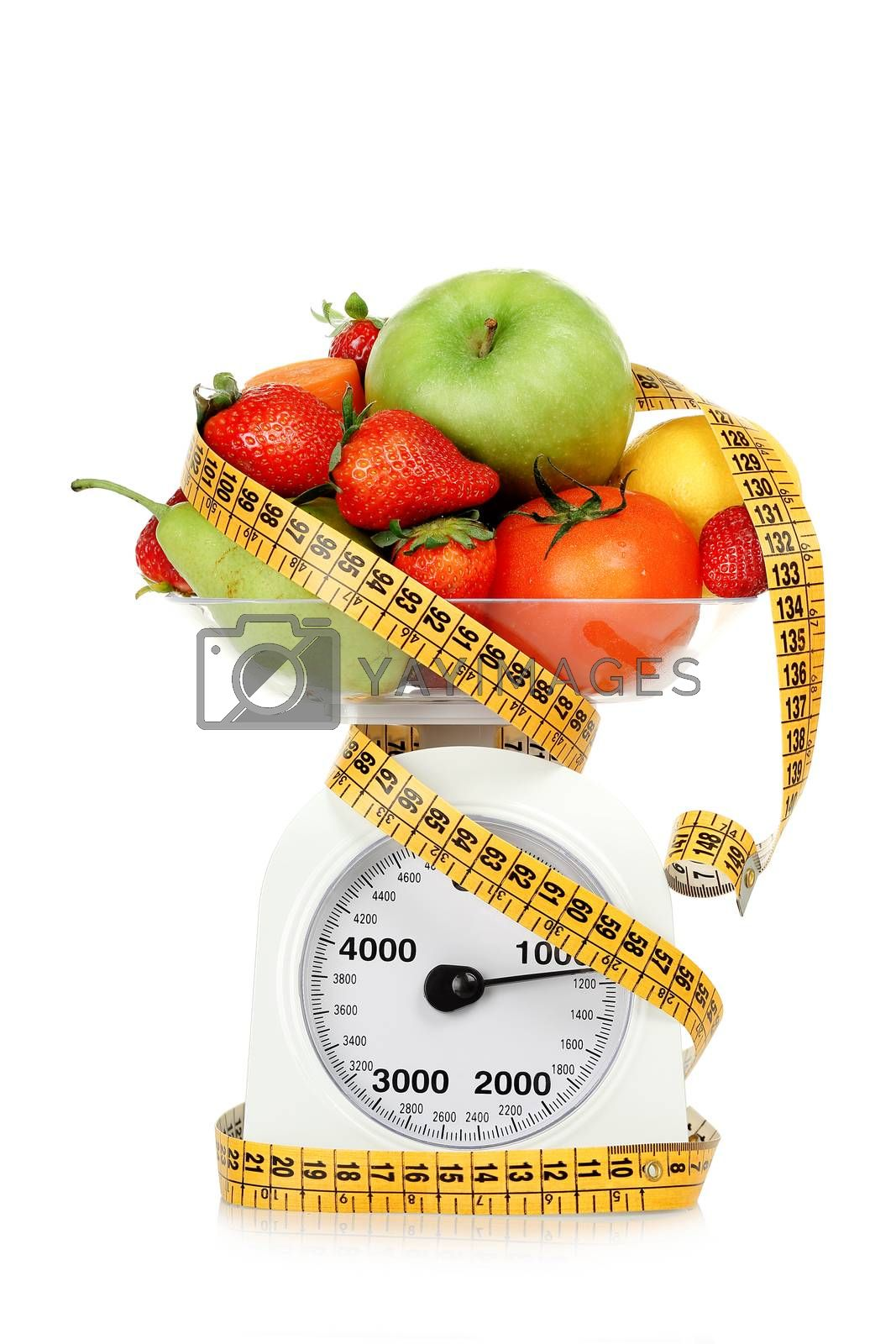 measuring tape around scales with fruits and vegetables, dieting concept