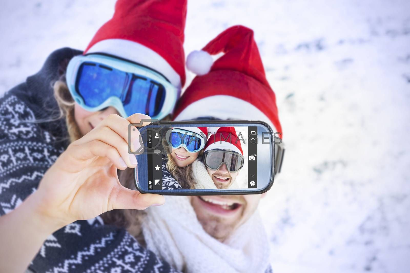 Hand holding smartphone showing against man piggybacking cheerful woman on snow
