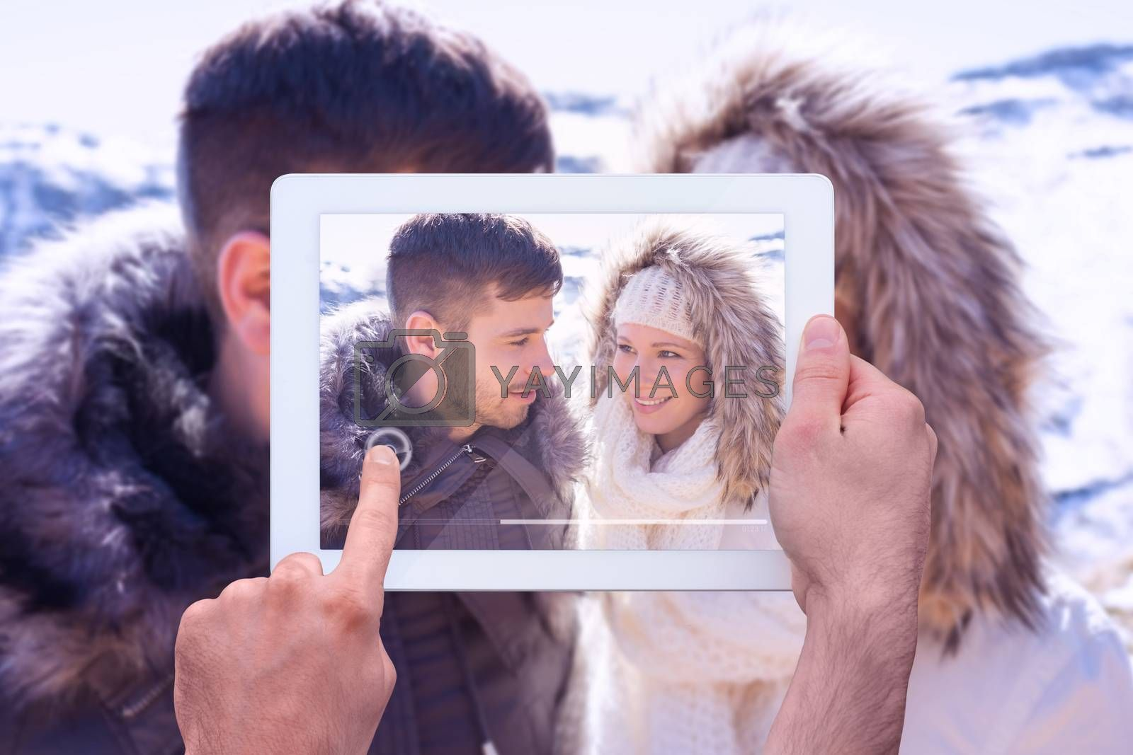 Hand holding tablet pc against couple in fur hood jackets against snowed mountain