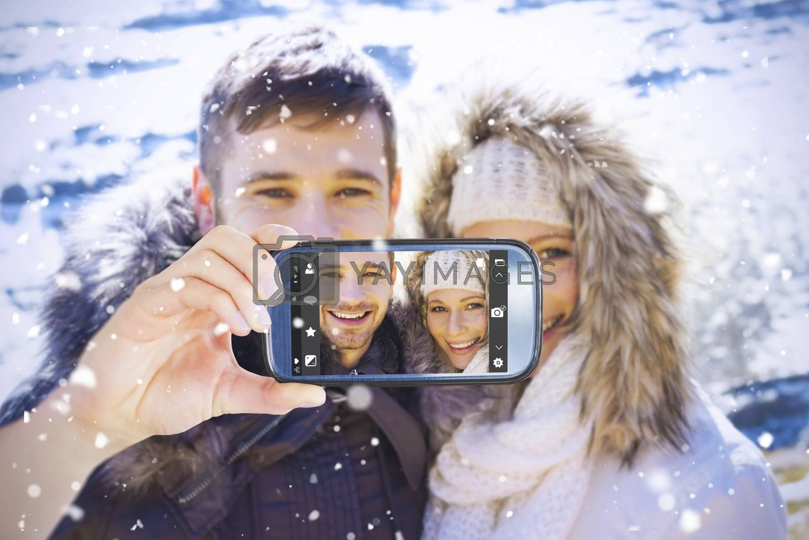 Hand holding smartphone showing against couple in fur hood jackets against snowed mountain range