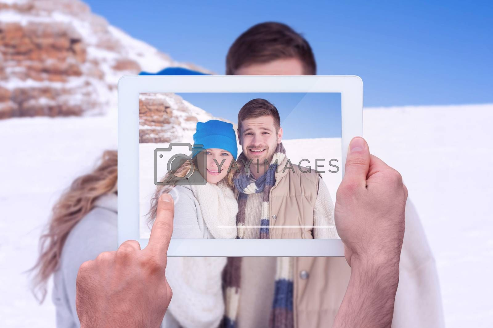 Hand holding tablet pc against couple in warm clothing on snow covered landscape