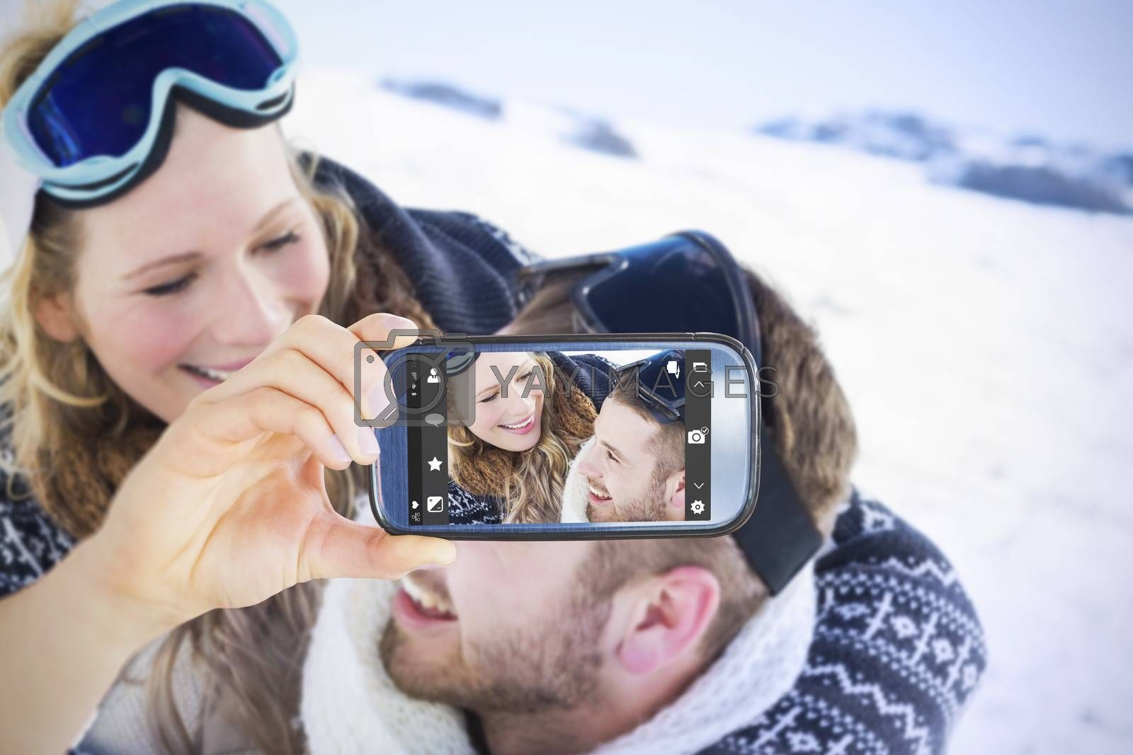 Hand holding smartphone showing against close up of a cheerful couple with ski goggles on snow