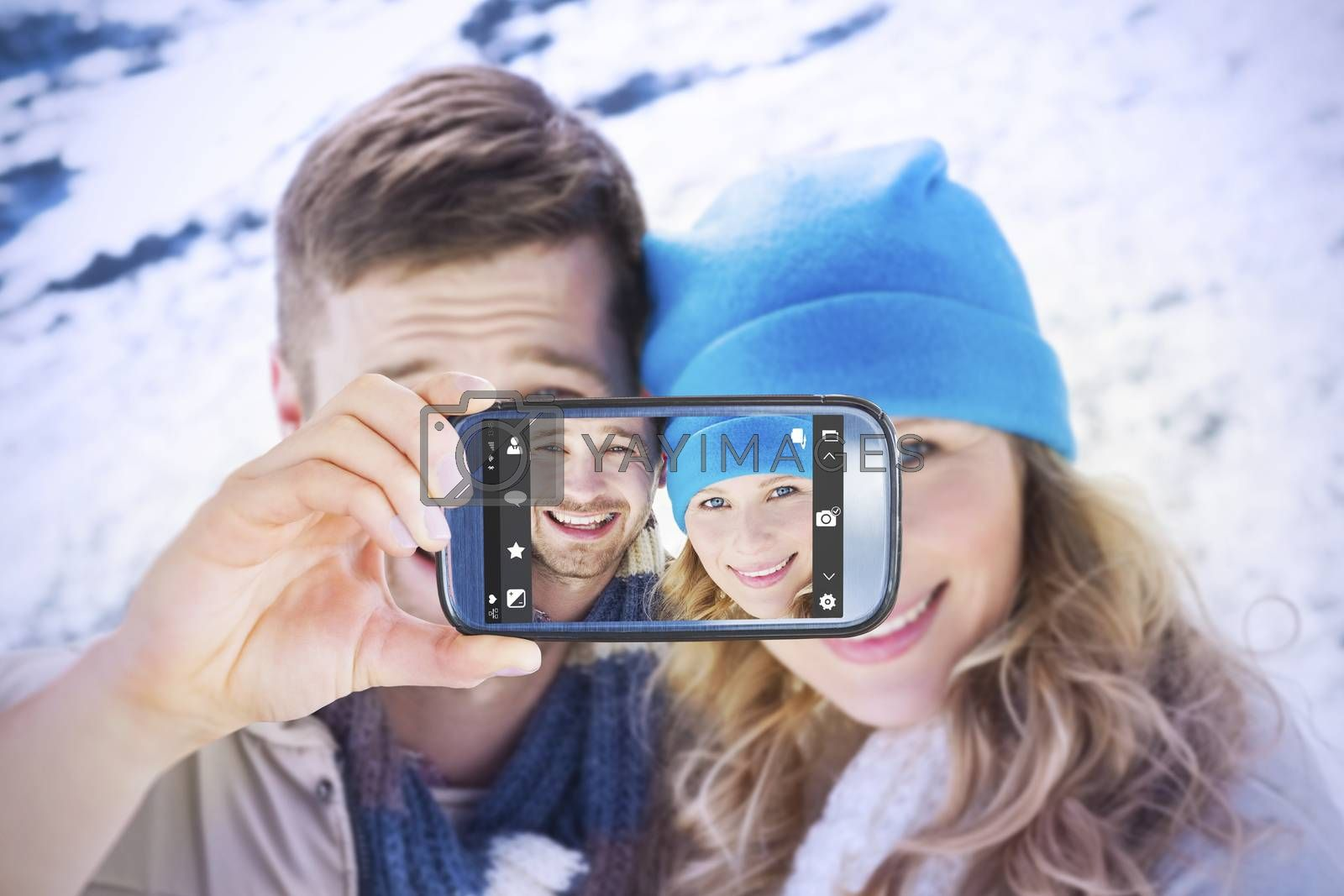Hand holding smartphone showing against loving couple in warm clothing on snow covered landscape