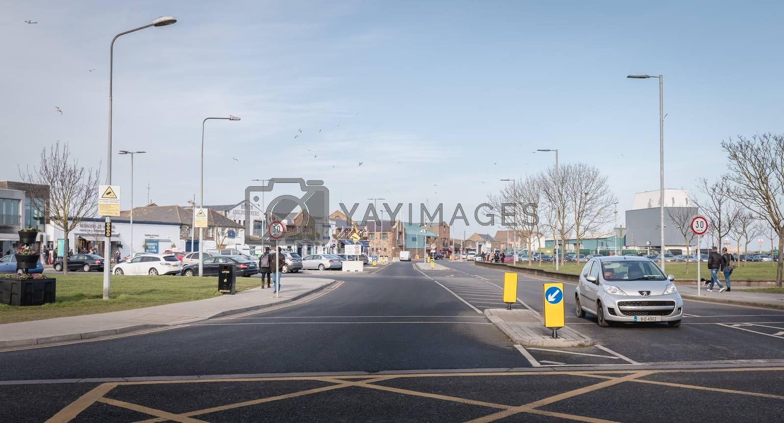 Howth, Ireland - February 15, 2019: people walking in the typical city center of a small fishing port near Dublin on a winter day