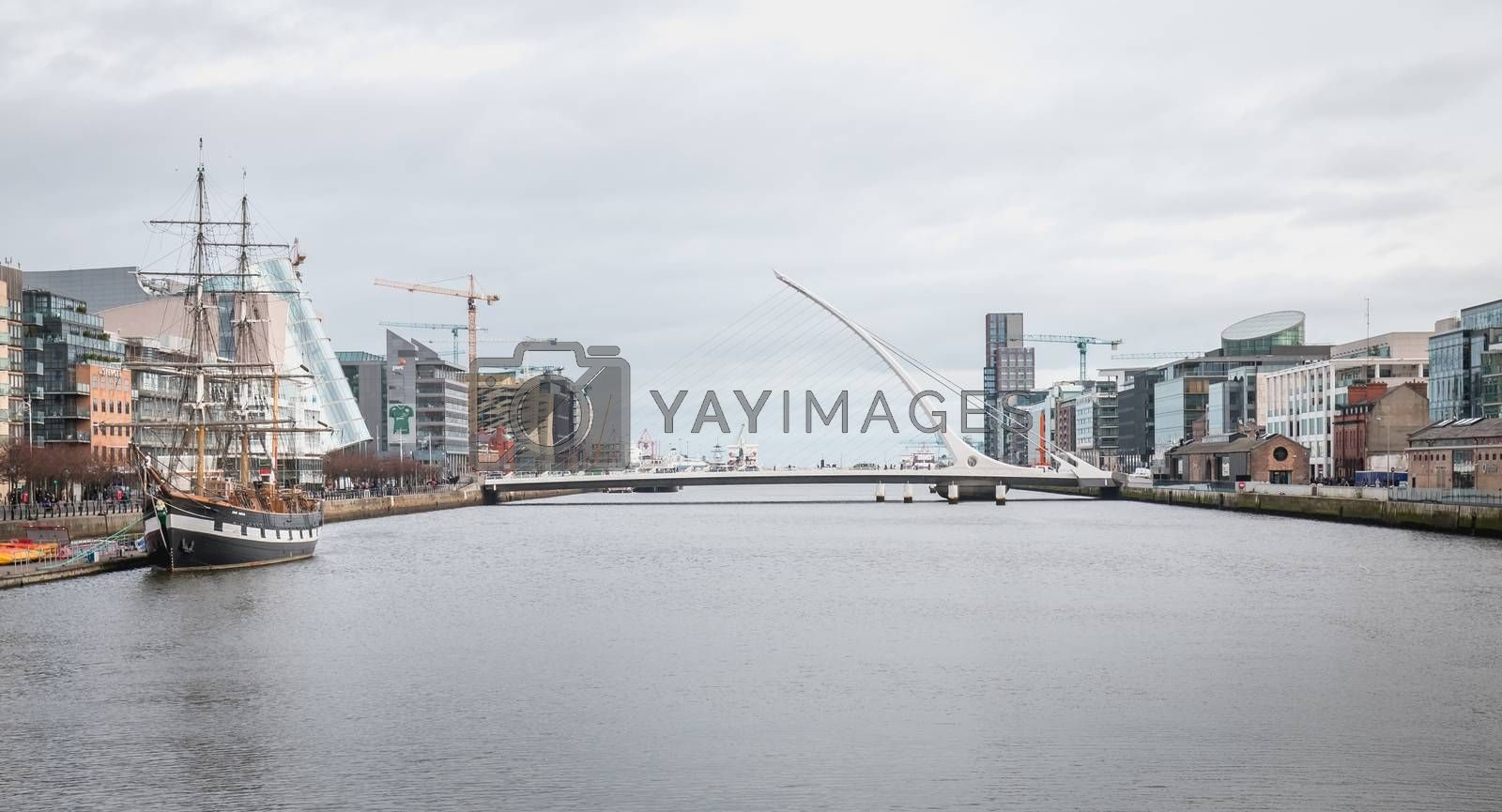 Dublin, Ireland - February 12, 2019: View of the River Liffey in the city center with the replica of the 3-mast sailboat Jeanie Johnston and the Samuel Beckett bridge on a winter day