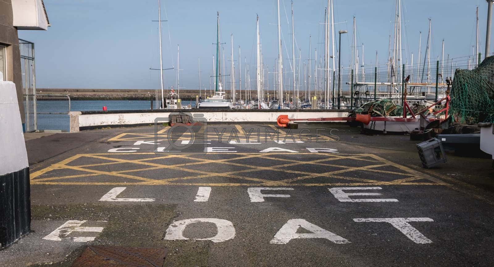 Howth near Dublin, Ireland - February 15, 2019: Keep clear life boat painting on bitumen from a boat care and maintenance area in the harbor on a winter day