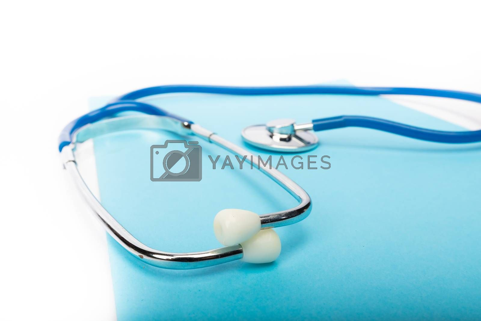 medical record and blue stethoscope close-up on white background in studio