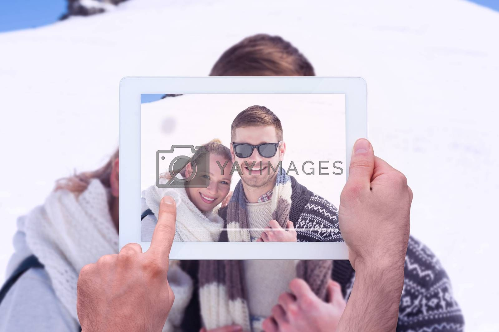 Hand holding tablet pc against smiling couple in front of snowed hill