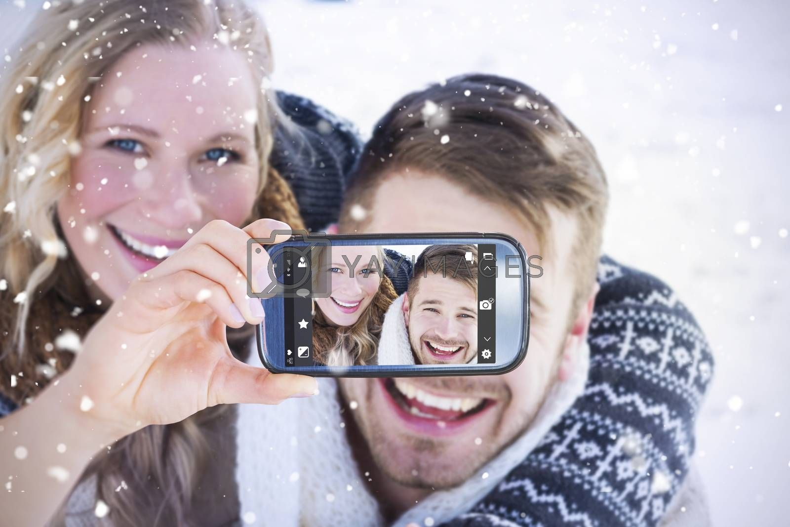 Hand holding smartphone showing against close up of a cheerful couple holding hands on snow