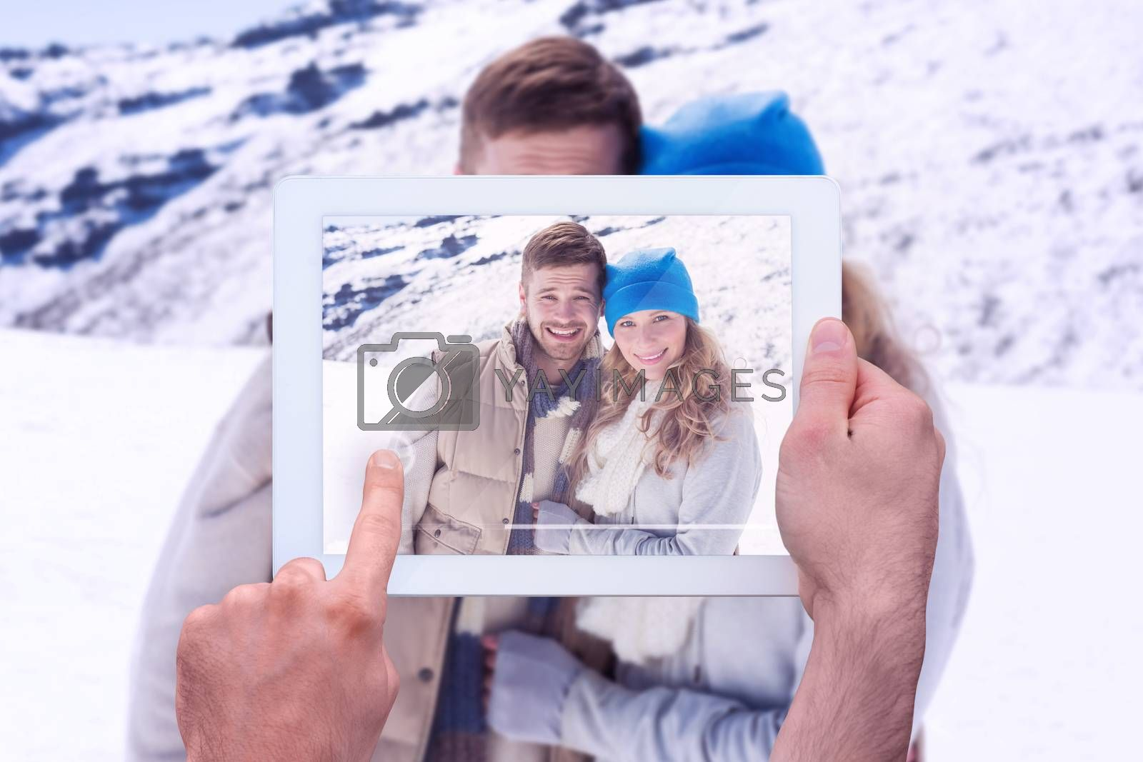Hand holding tablet pc against loving couple in warm clothing on snow covered landscape