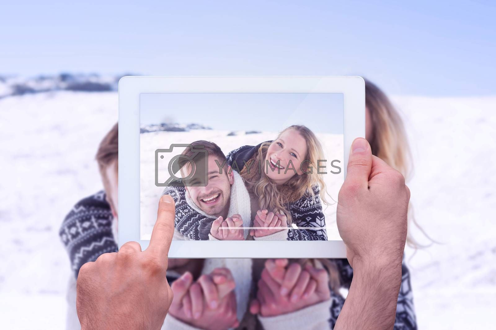 Hand holding tablet pc against close up of a cheerful couple holding hands on snow