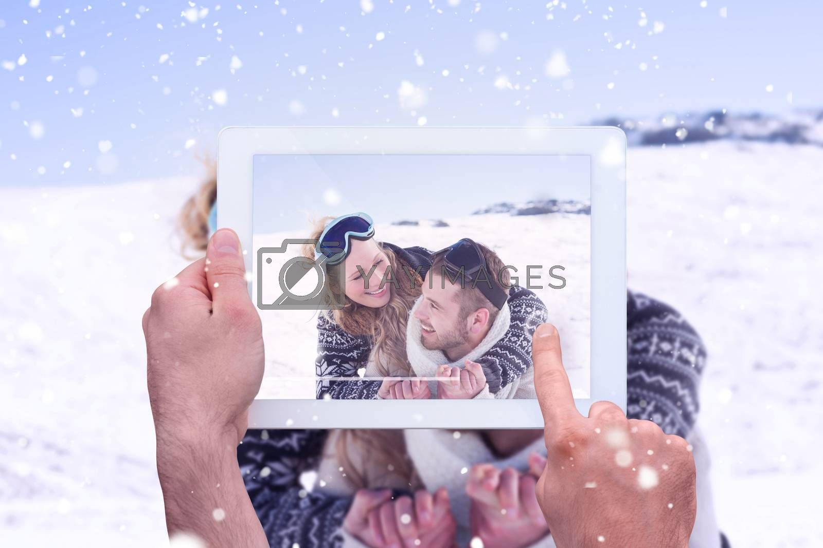 Hand holding tablet pc against close up of a cheerful couple with ski goggles on snow
