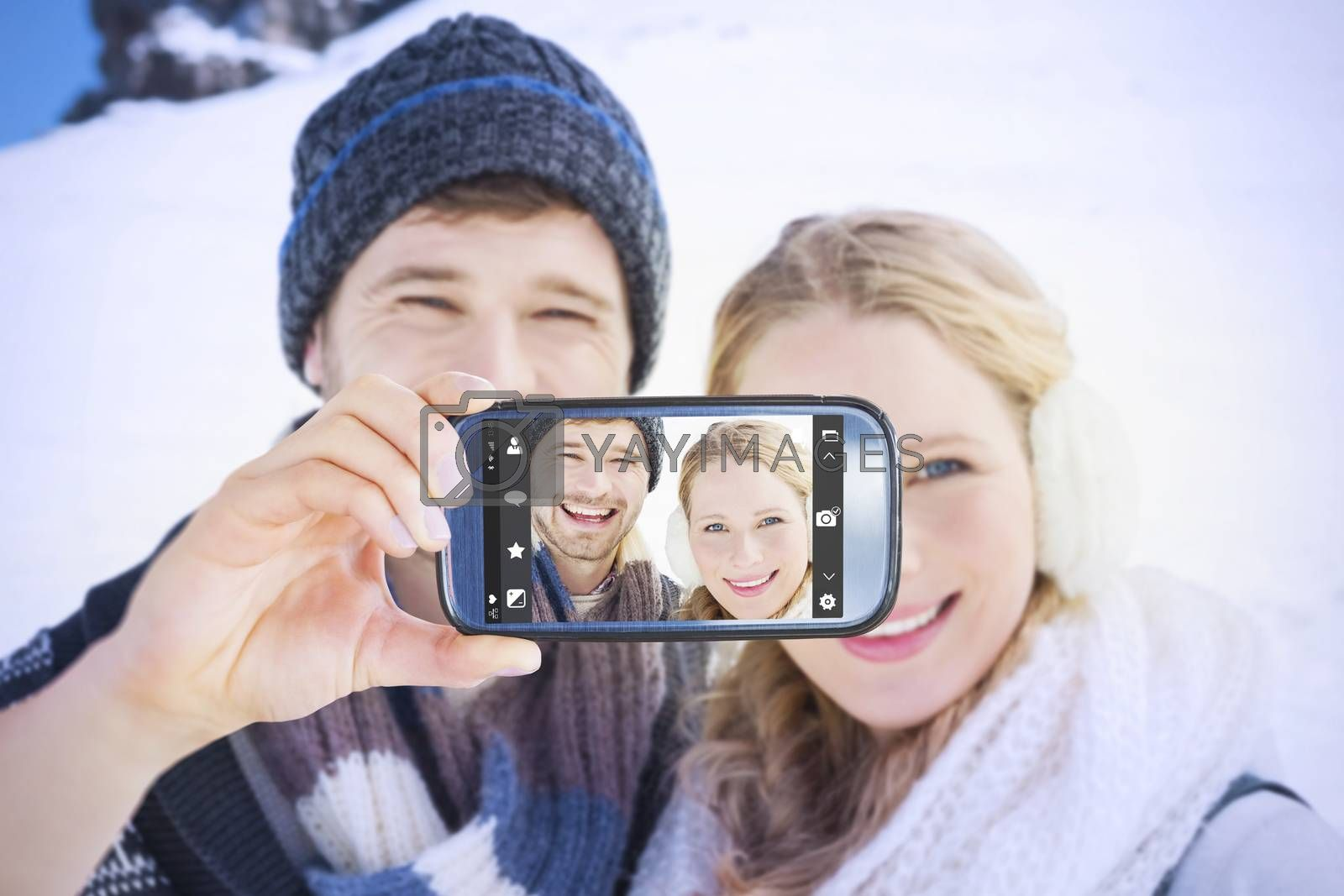 Hand holding smartphone showing against couple in front of snowed hill and clear blue sky