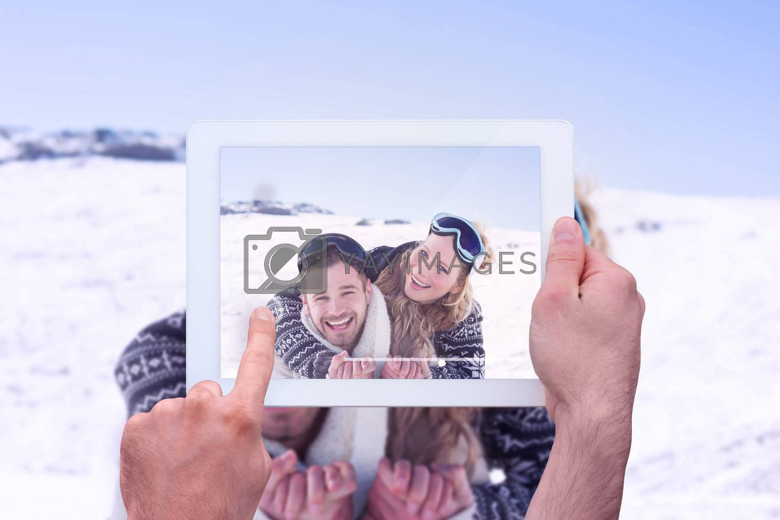 Hand holding tablet pc against cheerful couple with ski goggles on snow