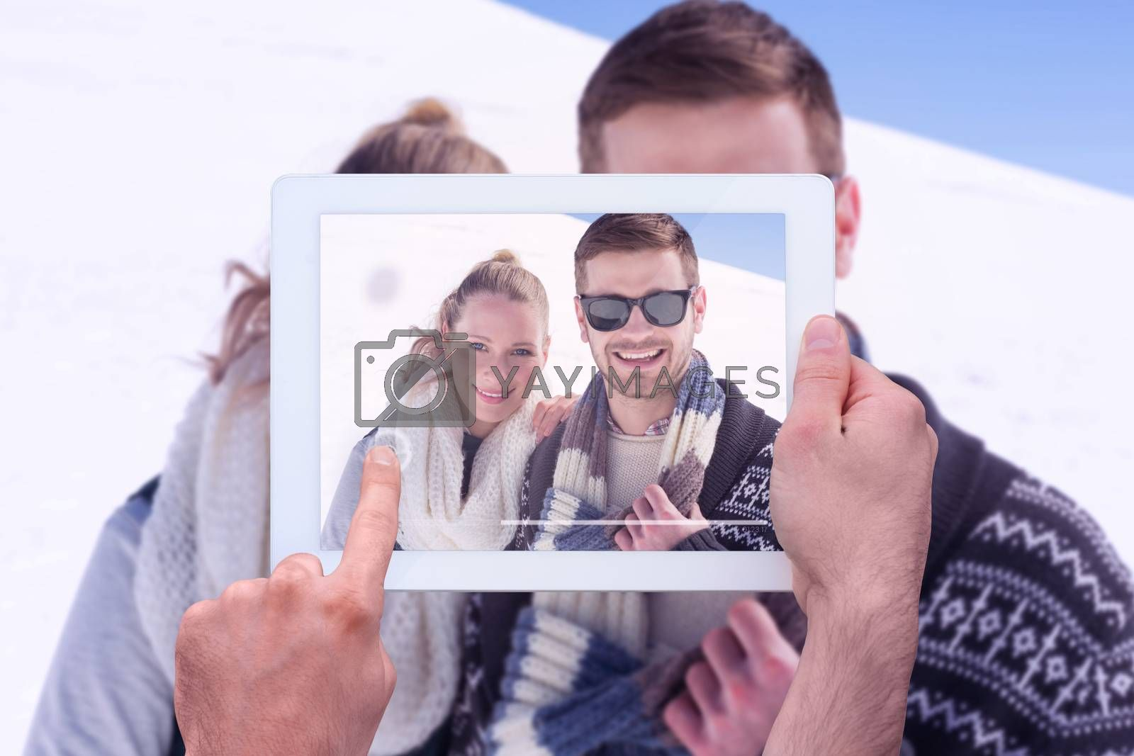 Hand holding tablet pc against smiling couple in warm clothing on snow covered landscape